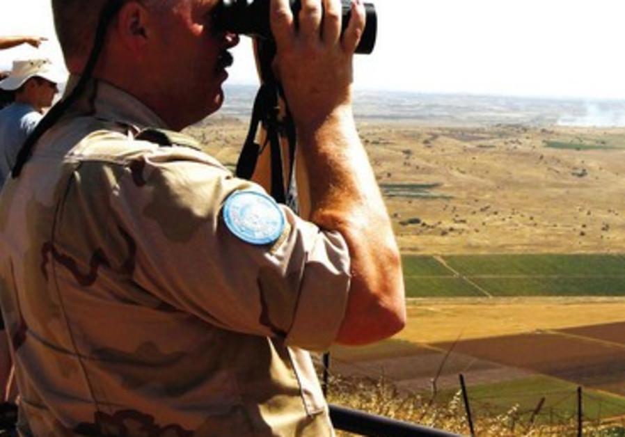 Un soldat de la paix observe les combats en Syrie depuis les hauteurs du Golan.