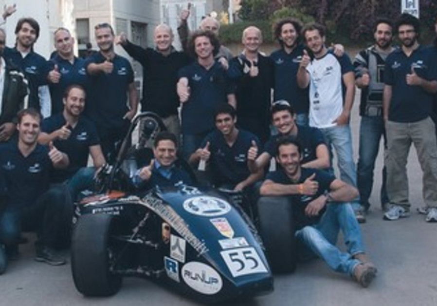 STUDENT ENGINEERS from BGU Racing pose with the Formula 1 race car they designed