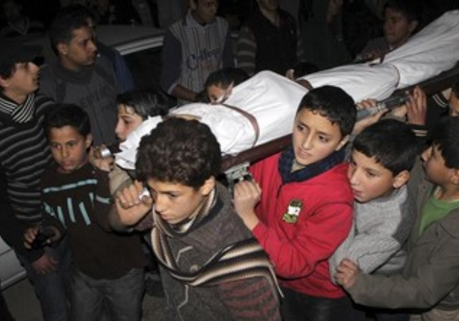 Children carry the body of a friend that was killed by shelling