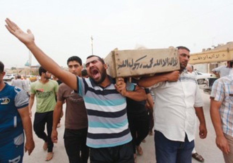 RELATIVES CARRY the coffin of an Iraqi police officer killed by Sunni insurgents in an attack.