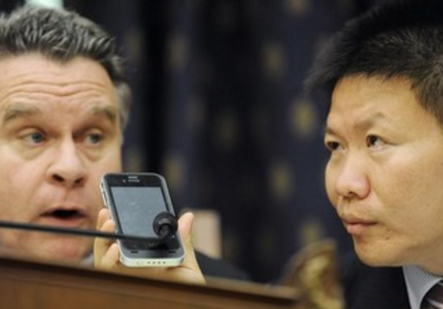 ChinaAid founder Bob Fu (R) helps US Rep. Chris Smith speak by phone with a blind Chinese dissident.