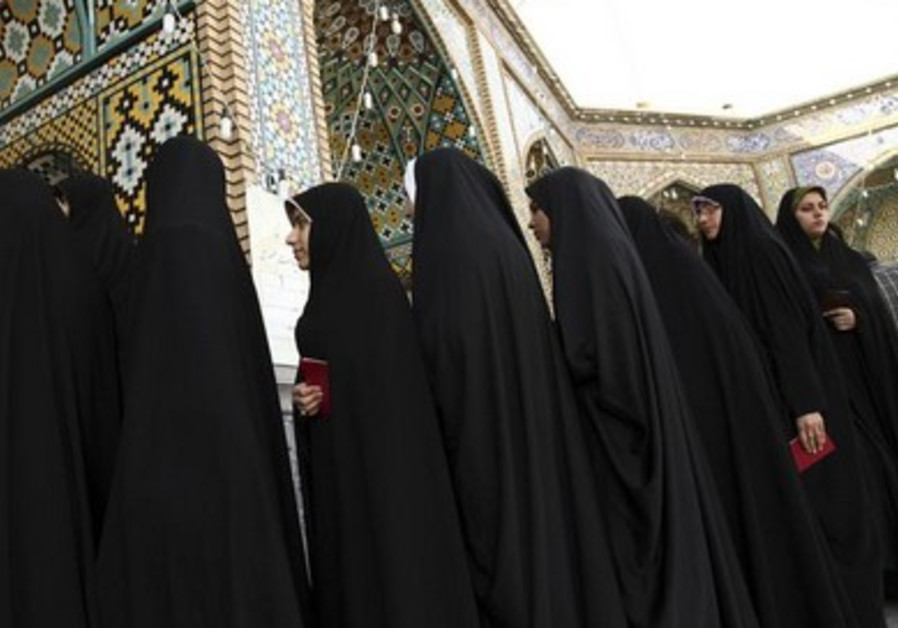 Women stand in line to vote during the Iranian presidential election