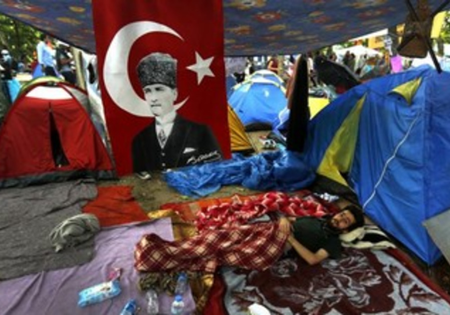 Protester rests next to tents in Gezi Park in Istanbul's Taksim square June 12, 2013.