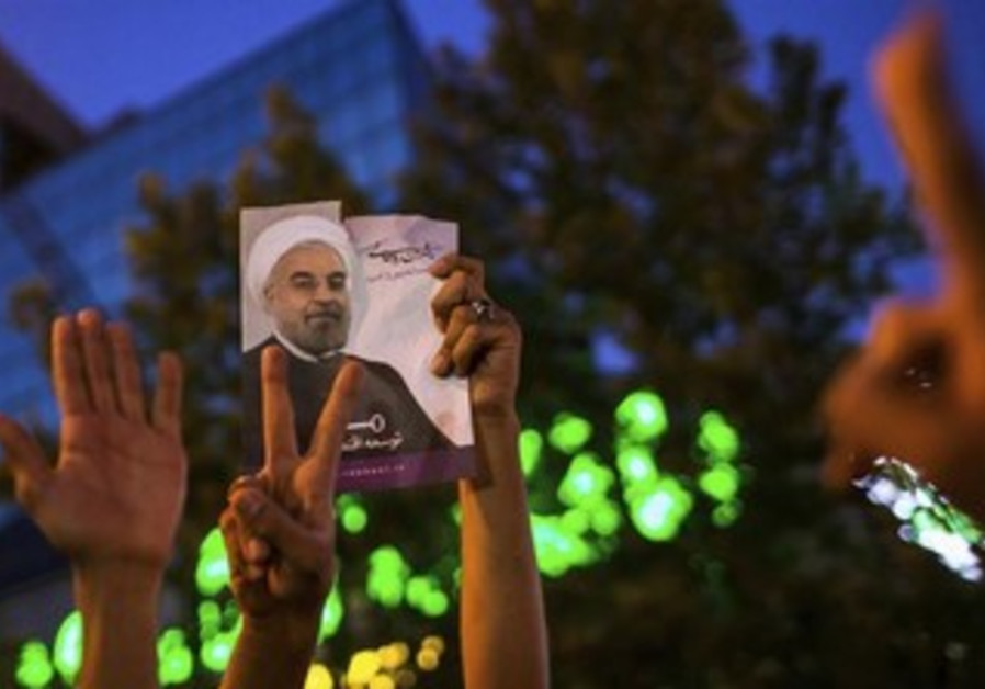 Supporters of Rohani hold a picture of him as they celebrate his victory in Tehran June 15, 2013.