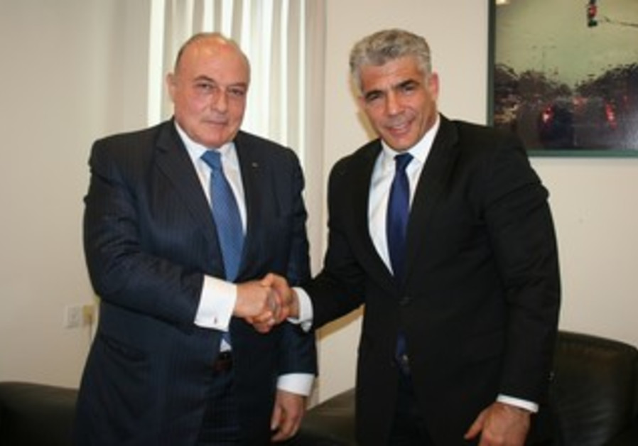 Finance Minister Yair Lapid shakes hands with his PA counter part  Shukri Bishara