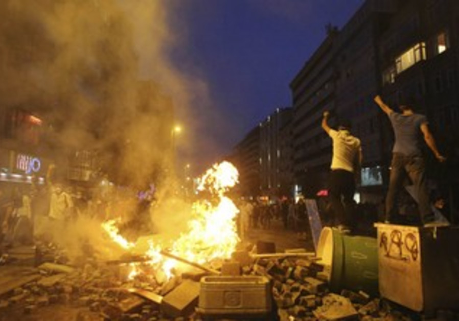 Anti-government protesters shout slogans as they stand on barricades in Istanbul June 16, 2013.
