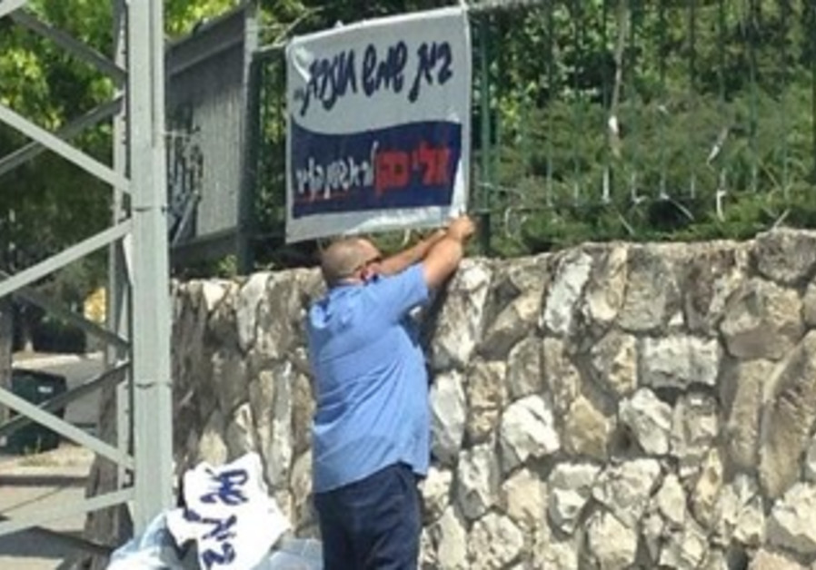 Eli Cohen campaign posted picture on Facebook of city worker removing campaign poster.