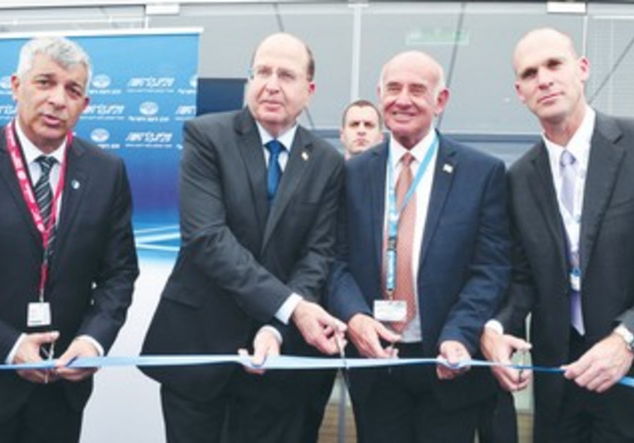 DEFENSE MINISTER Moshe Ya'alon cuts the ribbon to open the Israeli pavilion at the Paris Air Show