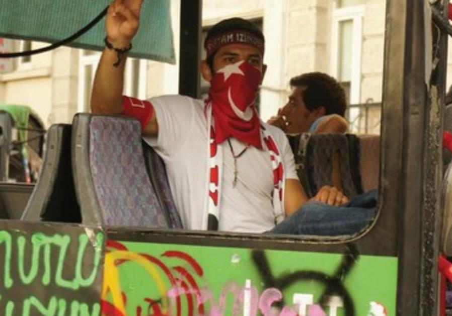 Un jeune proteste pacifiquement dans un bus brûlé, place Taskim.