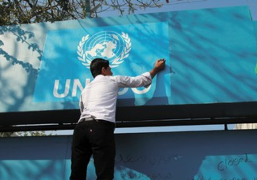 A PALESTINIAN youth stands on a ladder next to the UNESCO offices in the Gaza Strip.