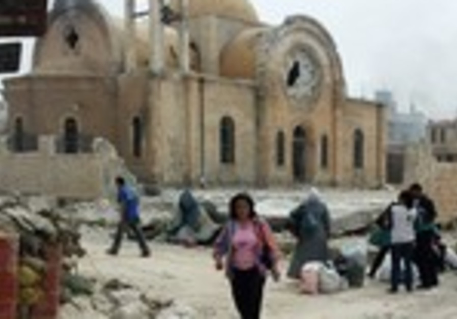 PEOPLE WALK past a ruined church in the Syrian town of Qusair.
