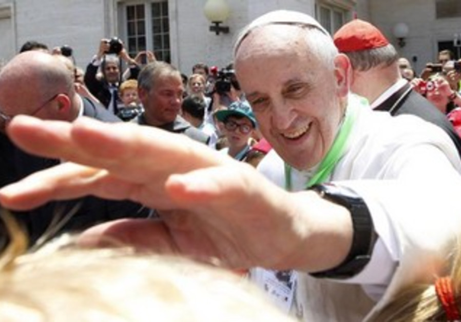 Pope Francis extends his hand.