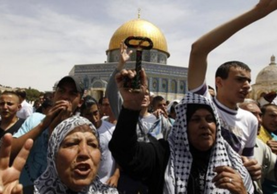 A Palestinian woman holds up a symbolic key as others take part in a protest after Friday prayers.