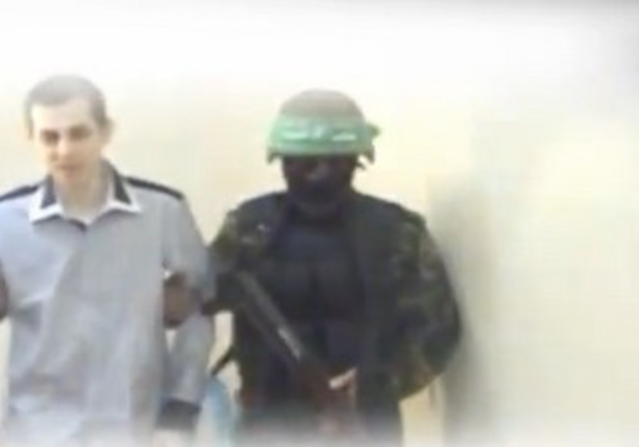 Gilad Schalit led by Hamas Kassam brigades man on his day of release.