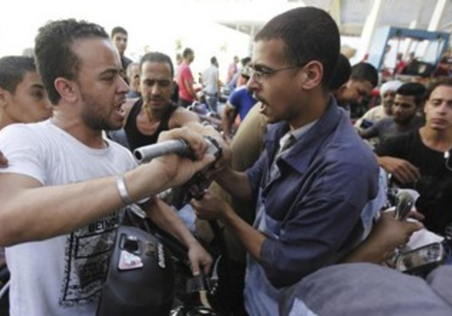 A man argues with a worker at a petrol station during a fuel shortage in Cairo June 26, 2013.