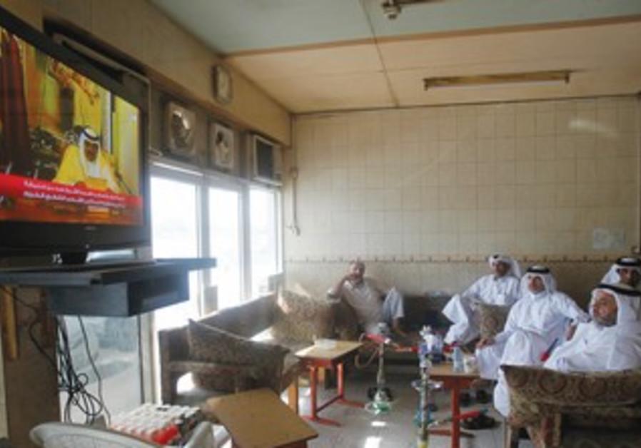 QATARI NATIONALS watch the speech of Qatar's Emir Sheikh Hamad bin-Khalifa al-Thani on TV