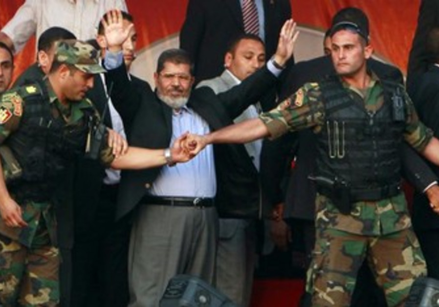 Egyptian President Morsi waves to supporters while surrounded by members of the presidential guard