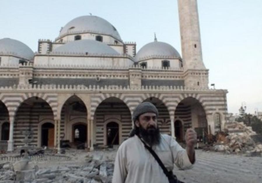 A FSA fighter gestures in front of damaged Khalid bin al Walid Mosque in Homs June 30, 2013.