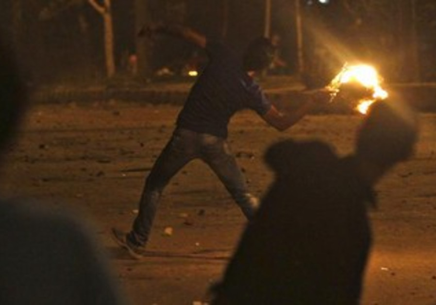 Protesters opposing Egyptian President Mohamed Mursi throw Molotov cocktails and stones