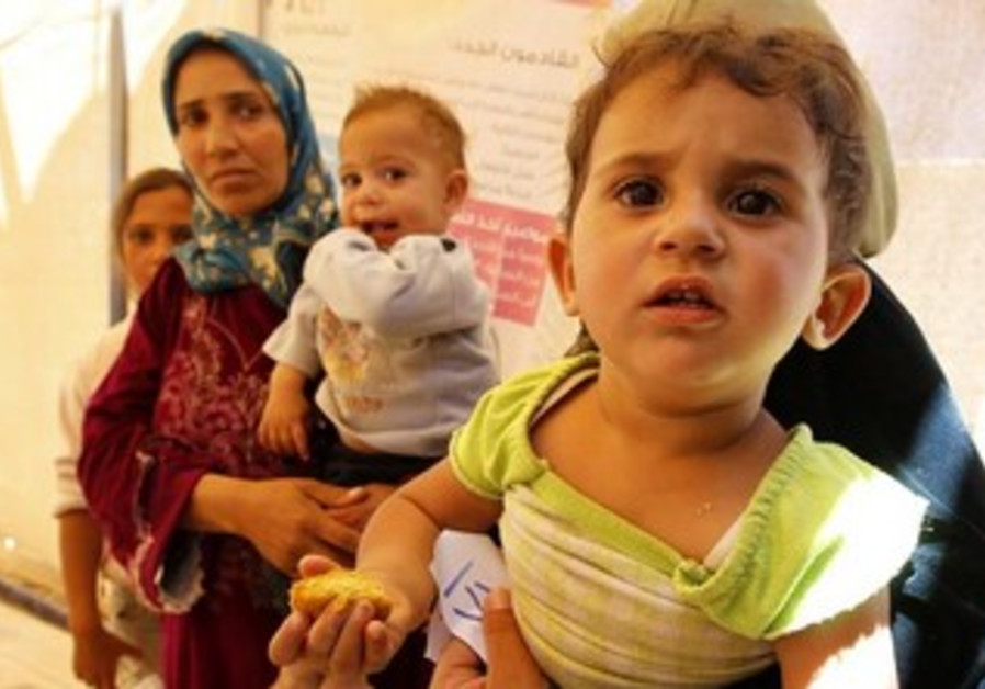 Syrian refugees wait for treatment at the Al Zaatri refugee camp in the Jordan