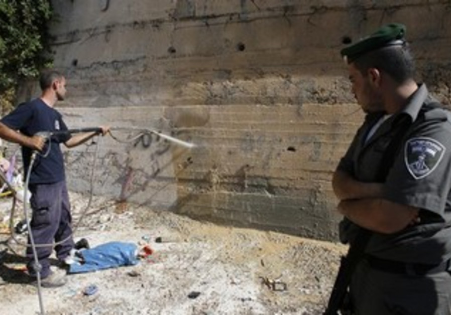 A border policeman watches man wash away price tag graffiti in east Jerusalem.