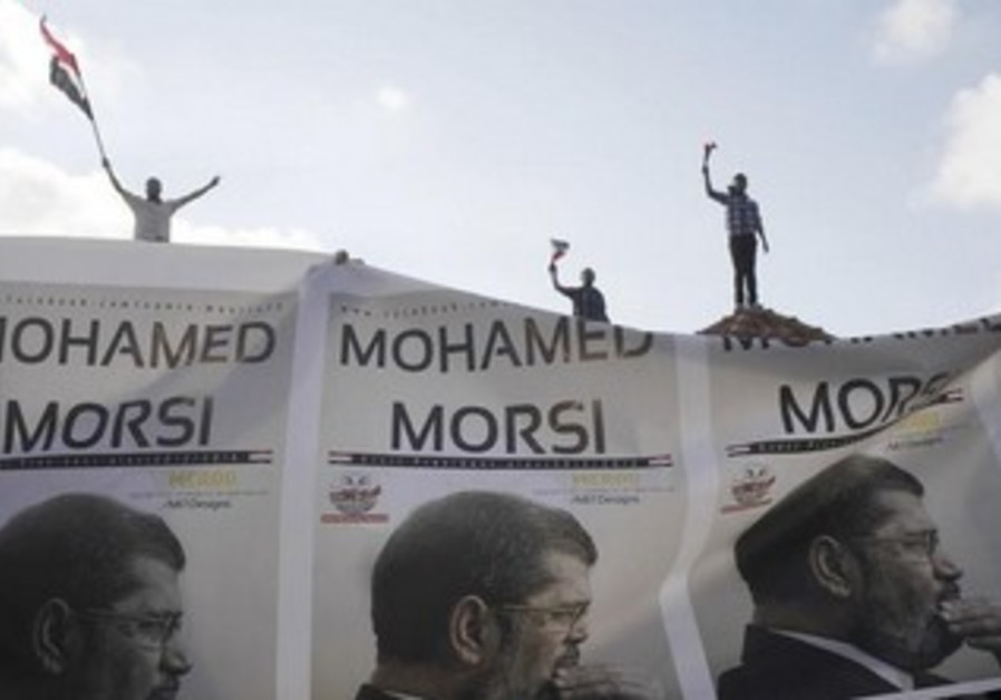 Supporters of President Mohamed Morsi carry a banner with his picture.