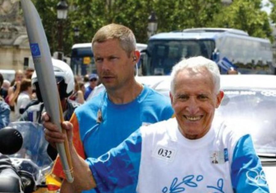 L'ancien champion français d'athlétisme lors du relai de la flamme olympique en 2004