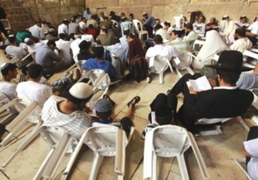 JEWISH MEN read Lamentations on Tisha Be'av, sitting on the ground as mourners, at the Western Wall