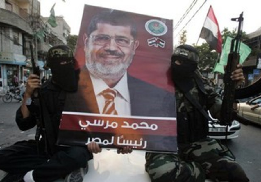 HAMAS GUNMEN hold a poster depicting Mohamed Morsi of the Muslim Brotherhood in Gaza City June 2012.