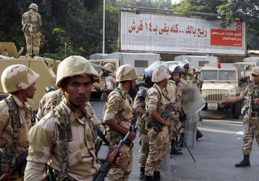 Army soldiers stand guard near supporters (not pictured) of overthrown President Mohamed Morsi.