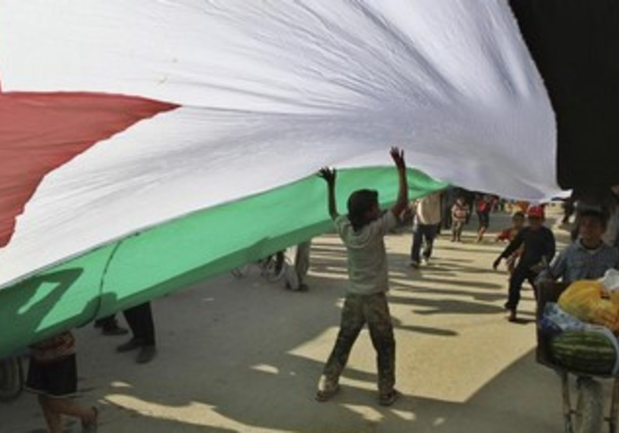 Syrian refugees hold a large Syrian opposition flag.