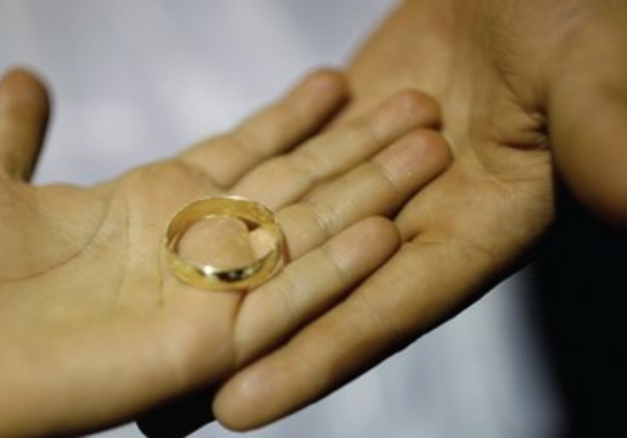 A COUPLE shows off one of their wedding rings.