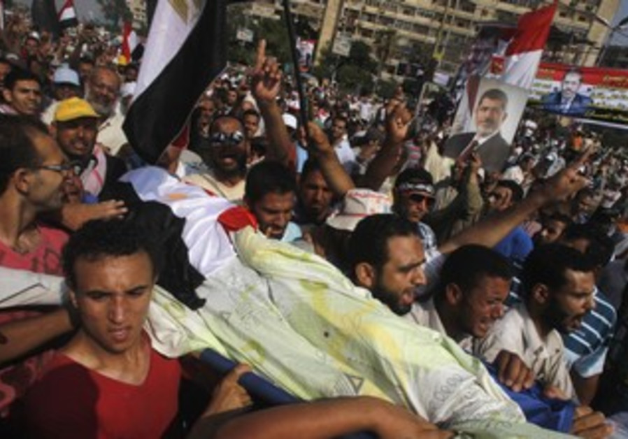 Morsi supporters carry body of man killed by violence outside the Republican Guard headquarters