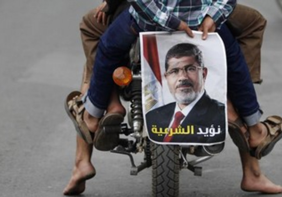 A pro-democracy supporter holds a picture of Morsi