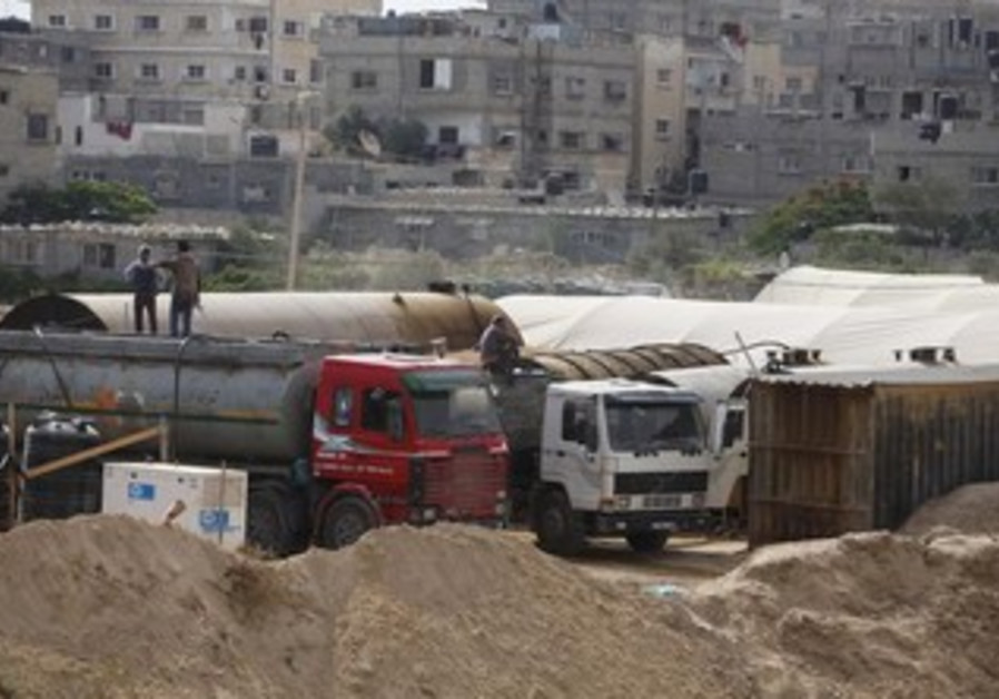 Palestinians fill tankers with fuel on the Egypt border
