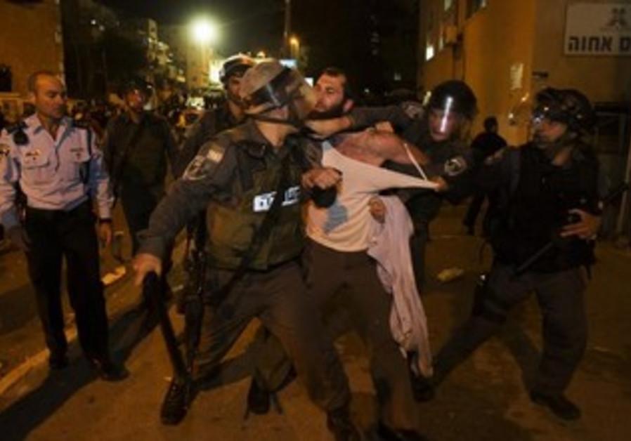 Israeli policemen detain an ultra-Orthodox Jewish man.