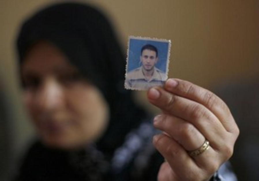 Wife of Palestinian Wael Abu Rida holding his picture.