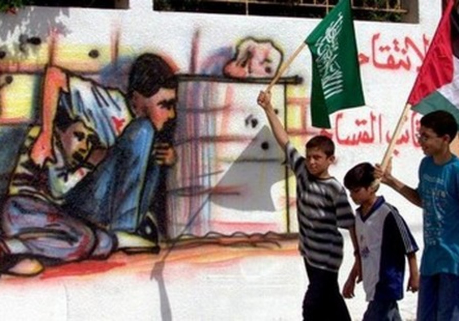 Palestinian boys carrying Hamas flags in the Gaza Strip walk past graffiti showing Muhammad al-Dura.