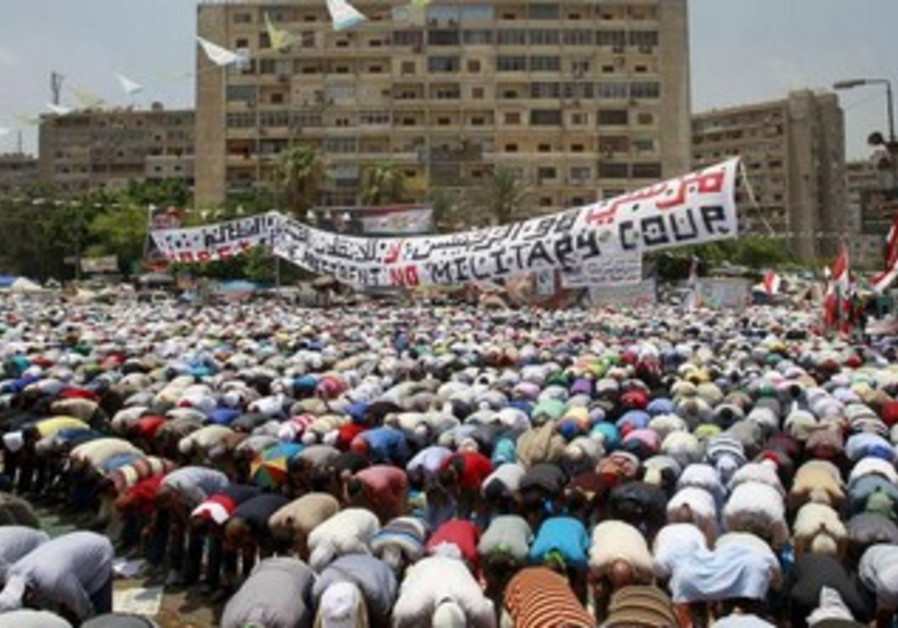 Morsi supporters perform weekly Friday prayers at Rabaa Adawiya square in Cairo, July 12, 2013.