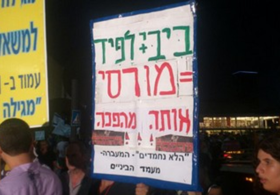 "Social justice protesters in Tel Aviv carry sign reading ""Bibi + Lapid = Morsi"", July 13, 2013"