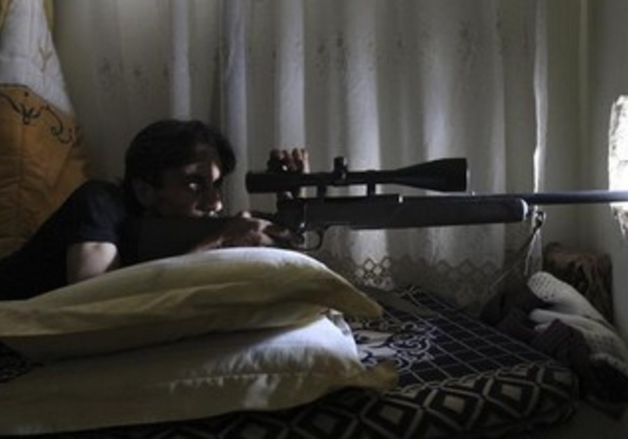 A Free Syrian Army fighter points his weapon as he takes up a position.