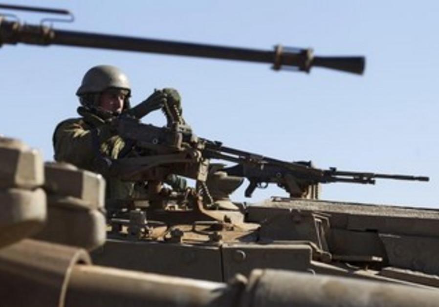 An Israeli soldier arranges ammunition atop a tank.