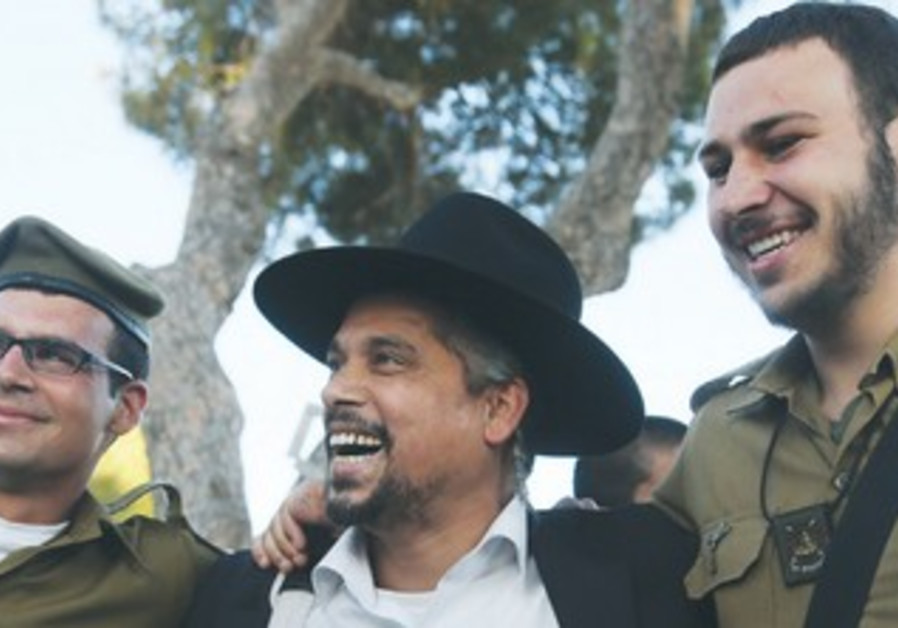 MAN CELEBRATES with soldiers from the Kfir Brigade's Netzah Yehuda Batallion.