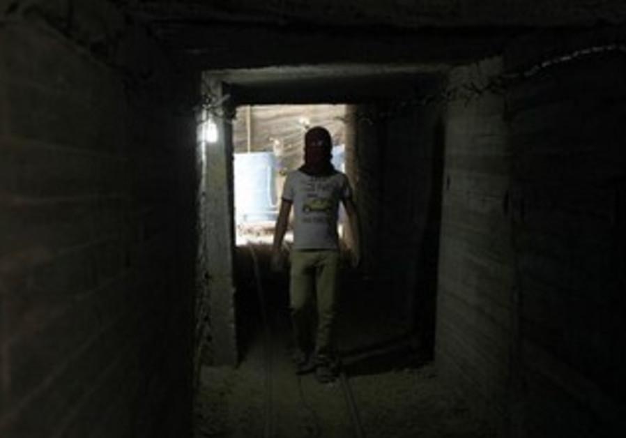 A Palestinian tunnel worker walks inside a smuggling tunnel dug beneath the Gaza-Egypt border
