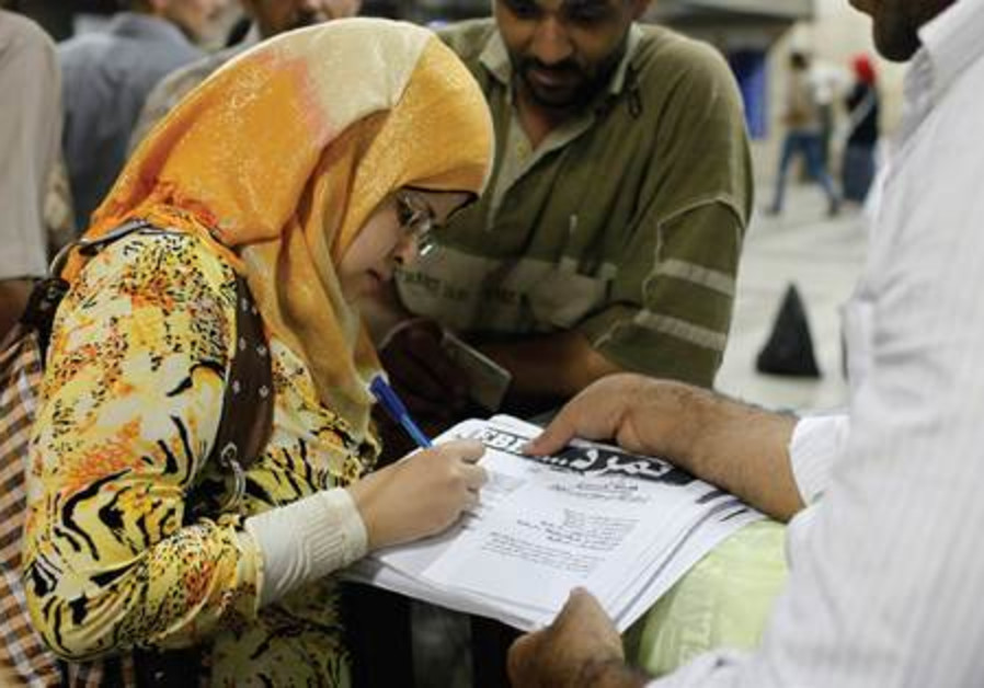 A woman signs petition in support of the anti-Morsi movement