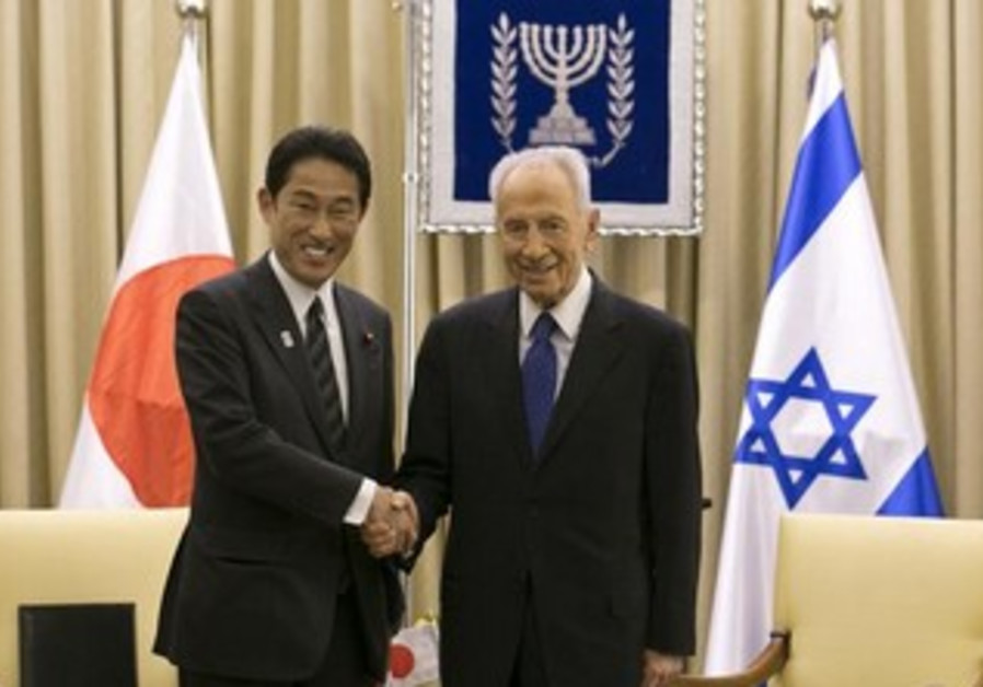 Shimon Peres (R) and Japan's Foreign Minister Fumio Kishida shake hands on July 24, 2013.