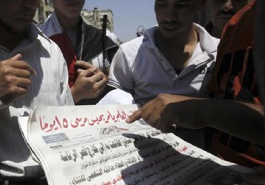 Muslim Brotherhood members and supporters of ousted Egyptian President Morsi read Al Ahram newspaper