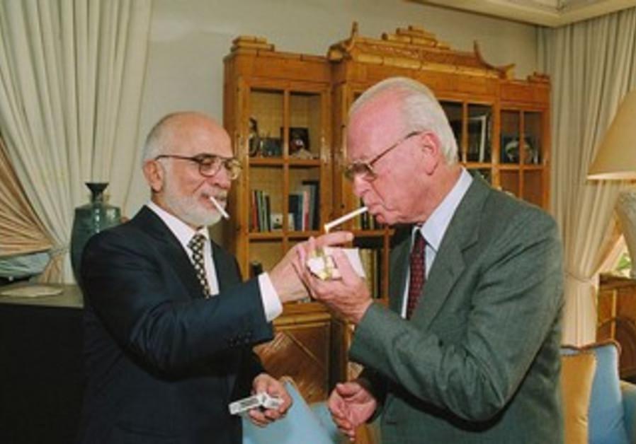 King Hussein of Jordan lights P.M.Yitzhak Rabin's cigarette at royal residence in Aqaba.