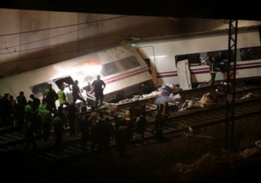 Rescue workers pull victims from a train crash near Santiago de Compostela, northwestern Spain, July