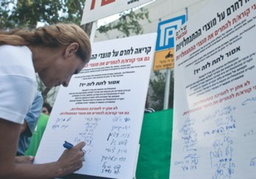 Woman signs Peace Now petition against settlements